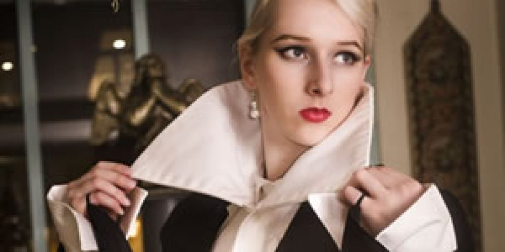 Frak černý sbílou vestou, vysokým límcem adlouhými rozšířenými rukávy – odepínací krovky